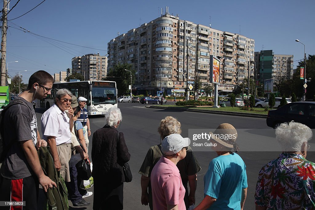 People wait for a bus as communist-era apartment buildings loom behind in Titan district on September 7, 2013 in Bucharest, Romania.
