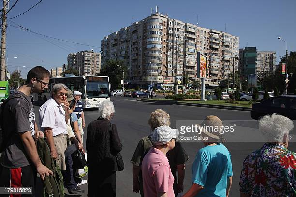 People wait for a bus as communistera apartment buildings loom behind in Titan district on September 7 2013 in Bucharest Romania