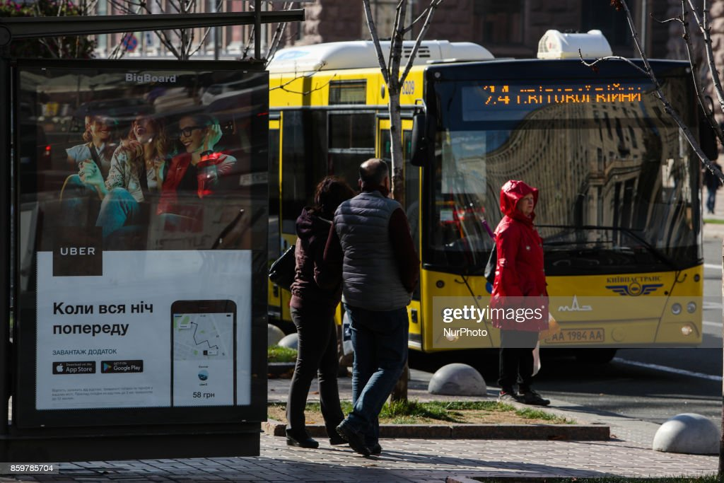 People wait for a bus at the bus stop branded with Uber Taxi service ad at Khreshchatyk str. in Kyiv, Ukraine, October 10, 2017.