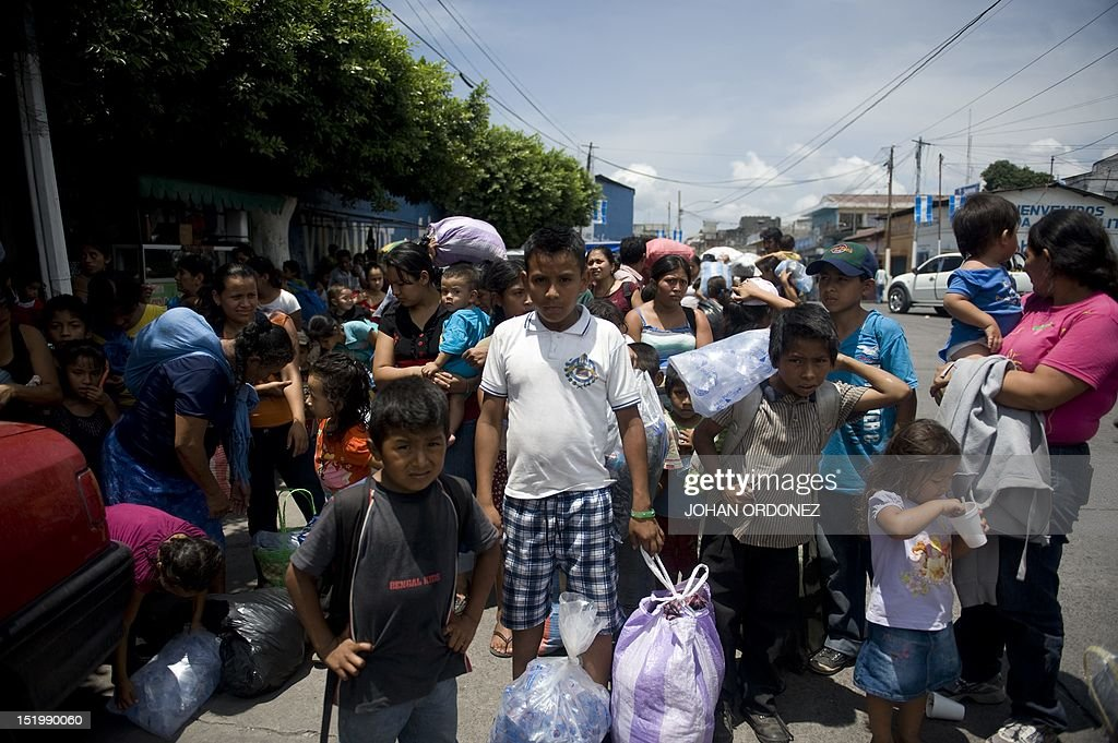 People wait for a bus in Santa Lucia, Escuintla, on September 14, 2012 to go back to their homes in Morelia, Chimaltenango, south Guatemala City, a day after being evacuated following the eruption of the Volcan de Fuego. Eruptions at Guatemala's Volcano of Fire weakened Friday, one day after powerful blasts sent columns of smoke and ash high into the sky and forced authorities to order a mass evacuation. The number and intensity of eruptions had dropped to the point that emergency officials said they could allow some of the people ordered to flee on Thursday to return home. Authorities said they evacuated about one-third of the 33,000 area residents that they were prepared to shelter if eruptions intensified. AFP PHOTO/Johan ORDONEZ