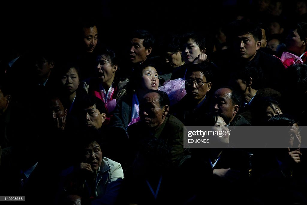 People wait for a fireworks display to mark 100 years since the birth of North Korea's founder Kim Il-Sung in Pyongyang on April 15, 2012. North Korea's new leader Kim Jong-Un delivered his first public speech and vowed to push for 'final victory' for his impoverished state despite a failed rocket launch two days ago, as the country celebrated the 100th anniversary of former leader Kim Il-Sung. AFP PHOTO / Ed Jones