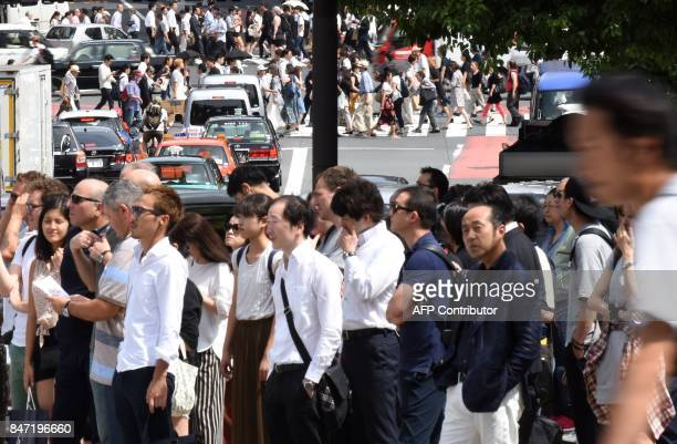 People wait for a green light to cross the street in Tokyo on September 15 2017 Millions of Japanese woke up in the early hours on September 15 as...