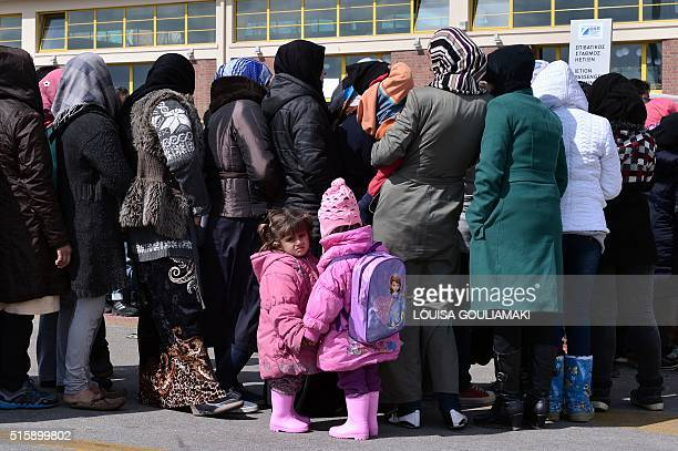 People wait for a red cross aid distribution at the port of Piraeus on March 16 2016 Some 4000 refugees and migrants are stranded in the port due to...