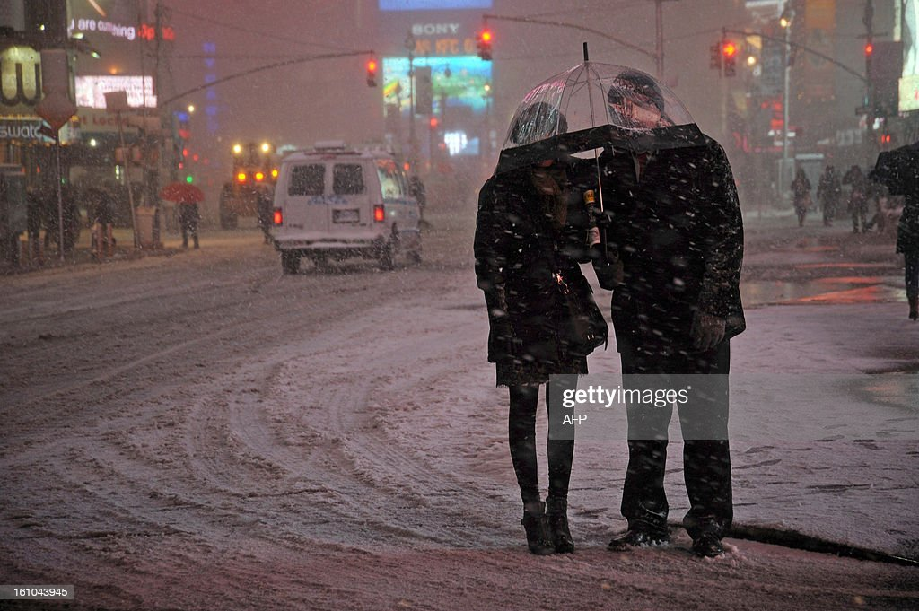 People wait for a taxi in the snow in Times Square in New York on February 8, 2013 during a storm affecting the northeast US. The storm was forecast to bring the heaviest snow to the densely-populated northeast corridor so far this winter, threatening power and transport links for tens of millions of people and the major cities of Boston and New York. New York and other regional airports saw more than 4,500 cancellations ahead of what the National Weather Service called 'a major winter storm with blizzard conditions' along most of the region's coastline.