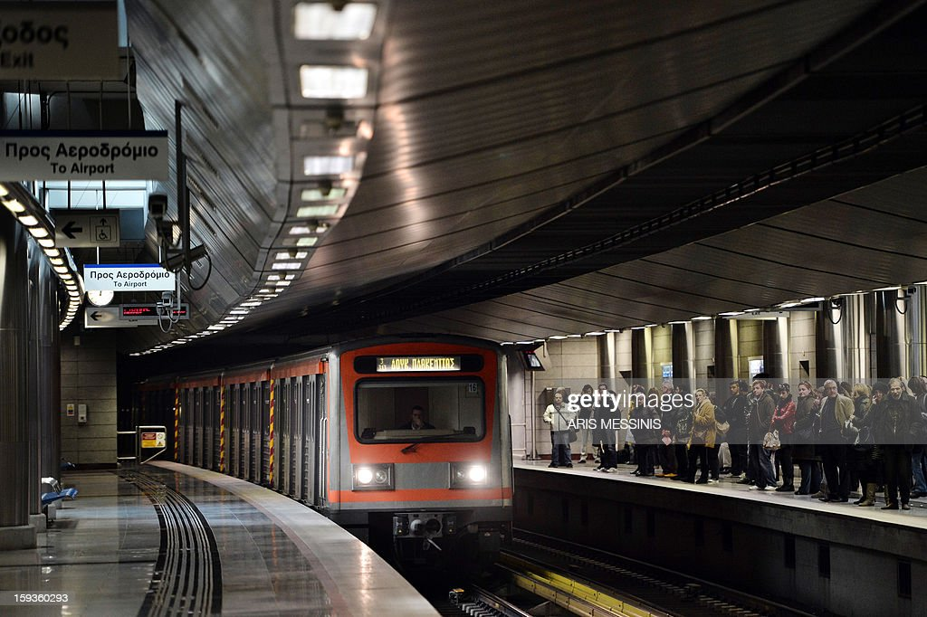 People wait for a train on a platform at an Athens' metro station on January 11, 2013. AFP PHOTO / ARIS MESSINIS