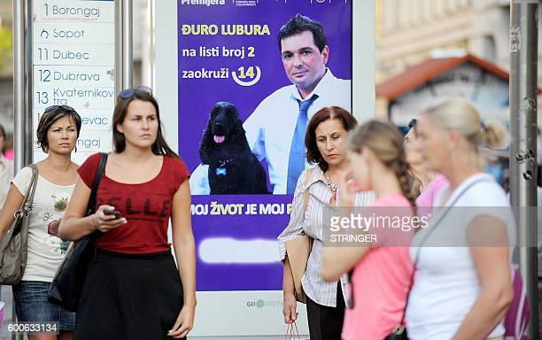People wait for a tram in front of a campaign poster for the Milan Bandic party in Zagreb on September 8 2016 Croatians will choose between two...