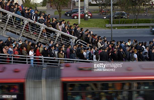People wait for a Transmilenio bus in Bogota Colombia on October 13 2015 Thousands of Colombians spend hours in the public transport service every...