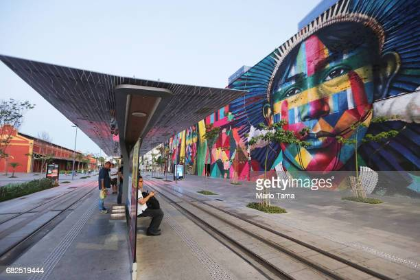 People wait for a VLT tram next to the famed mural painted by artist Eduardo Kobra for the Rio 2016 Olympic Games on May 12 2017 in Rio de Janeiro...