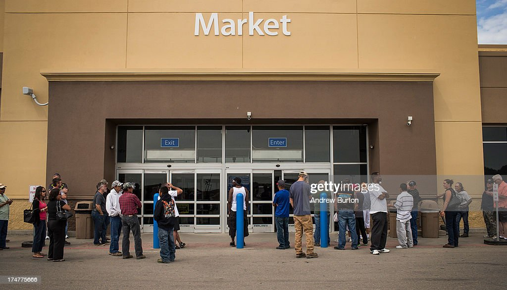 People wait for a Walmart to open on July 28, 2013 in Williston, North Dakota. North Dakota has been experiencing an oil boom in recent years, due in part to new drilling techniques including hydraulic fracturing and horizontal drilling. In April 2013, The United States Geological Survey released a new study estimating the Bakken formation and surrounding oil fields could yield up to 7.4 billion barrels of oil, doubling their estimate of 2008, which was stated at 3.65 billion barrels of oil.