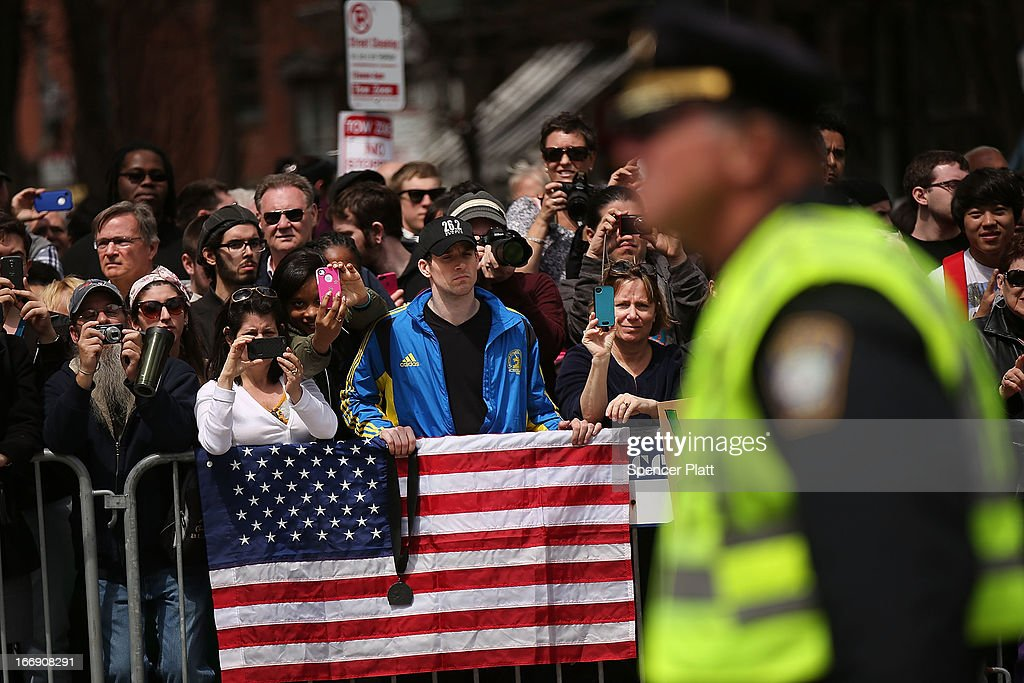 People wait for President Barack Obama's motorcade after he spoke at an interfaith prayer service for victims of the Boston Marathon attack titled 'Healing Our City,' at the Cathedral of the Holy Cross on April 18, 2013 in Boston, Massachusetts. Authorities investigating the attack on the Boston Marathon have shifted their focus to locating the person who placed a black bag down and walked away just before the bombs went off. The twin bombings at the 116-year-old Boston race, which occurred near the marathon finish line, resulted in the deaths of three people and more than 170 others injured.
