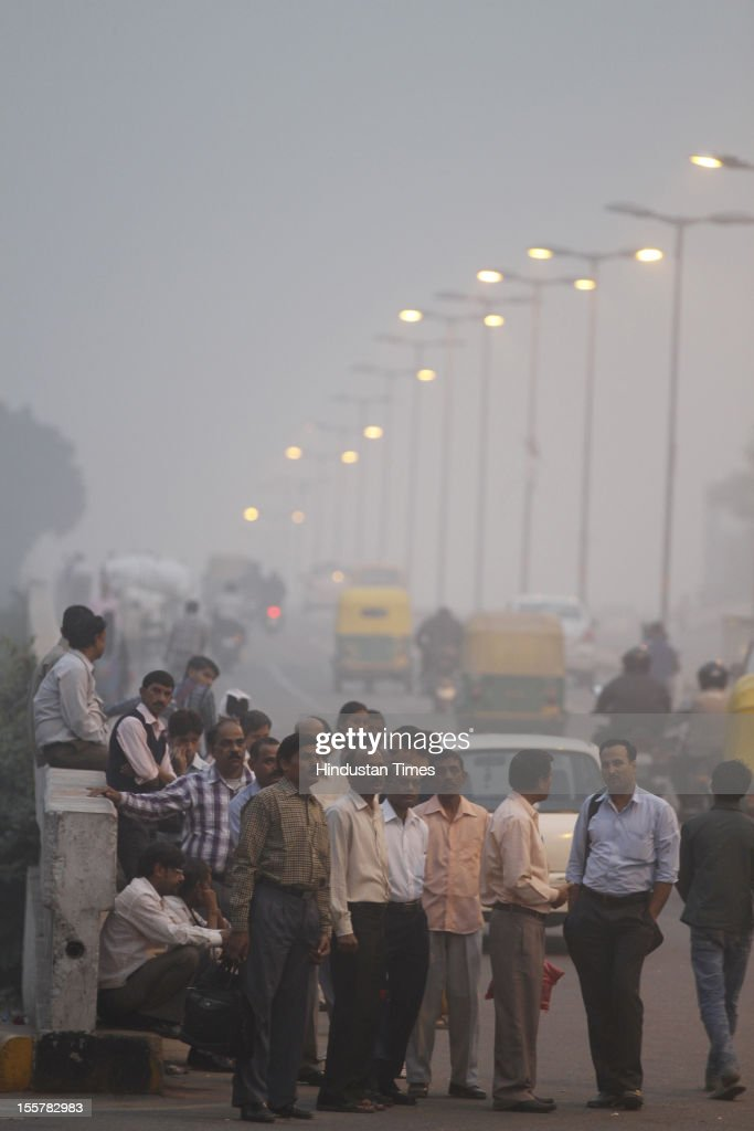 People wait for public transportation amid a blanket of smog, caused by a mixture of pollution and fog at NCR region on November 7, 2012 in New Delhi, India.