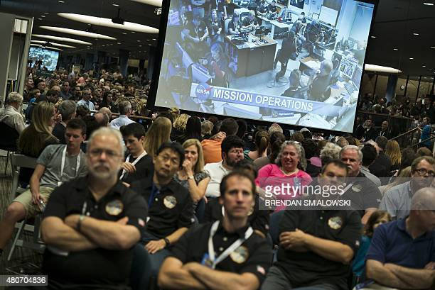 People wait for telemetry from the New Horizons probe at the Johns Hopkins University Applied Physics Laboratory July 14 2015 in Laurel Maryland The...