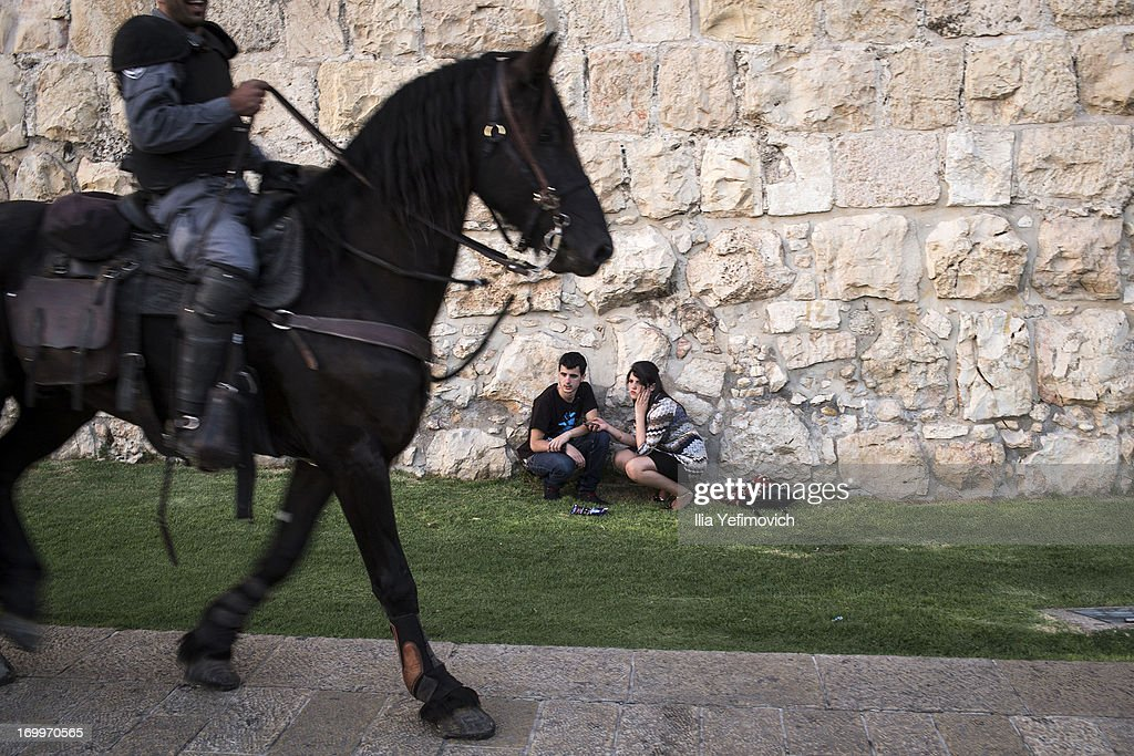 People wait for the annual Jerusalem Festival of Light on June 5, 2013 in Jerusalem, Israel. During the festival light installations are projected onto the historic buildings of Jerusalem's Old City.