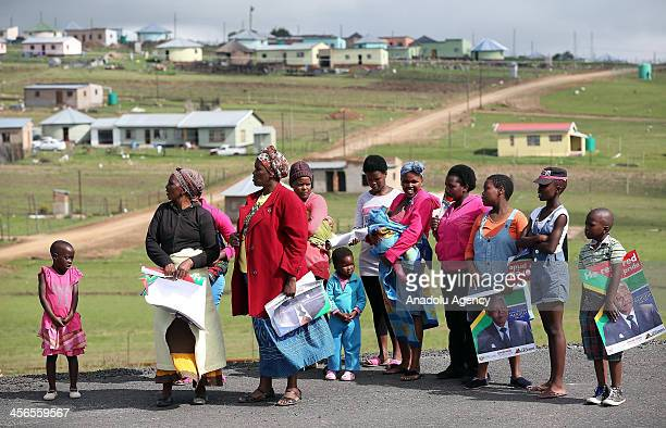 People wait for the arrival of funeral cortege of former South African President Nelson Mandela to his rural home in Qunu village in the Eastern Cape...
