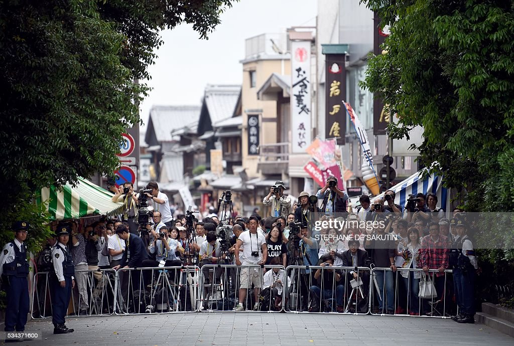 People wait for the arrival of G7 leaders outside Ise-Jingu Shrine in the city of Ise in Mie prefecture, on May 26, 2016 on the first day of the G7 leaders summit. World leaders kicked off two days of G7 talks in Japan on May 26 with the creaky global economy, terrorism, refugees, China's controversial maritime claims, and a possible Brexit headlining their packed agenda. / AFP / STEPHANE