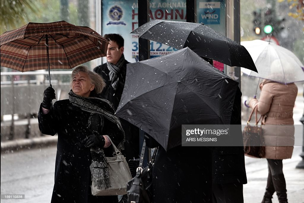 People wait for the bus at a bus station during a snowfall in Athens on January 8, 2013. AFP PHOTO / ARIS MESSINIS