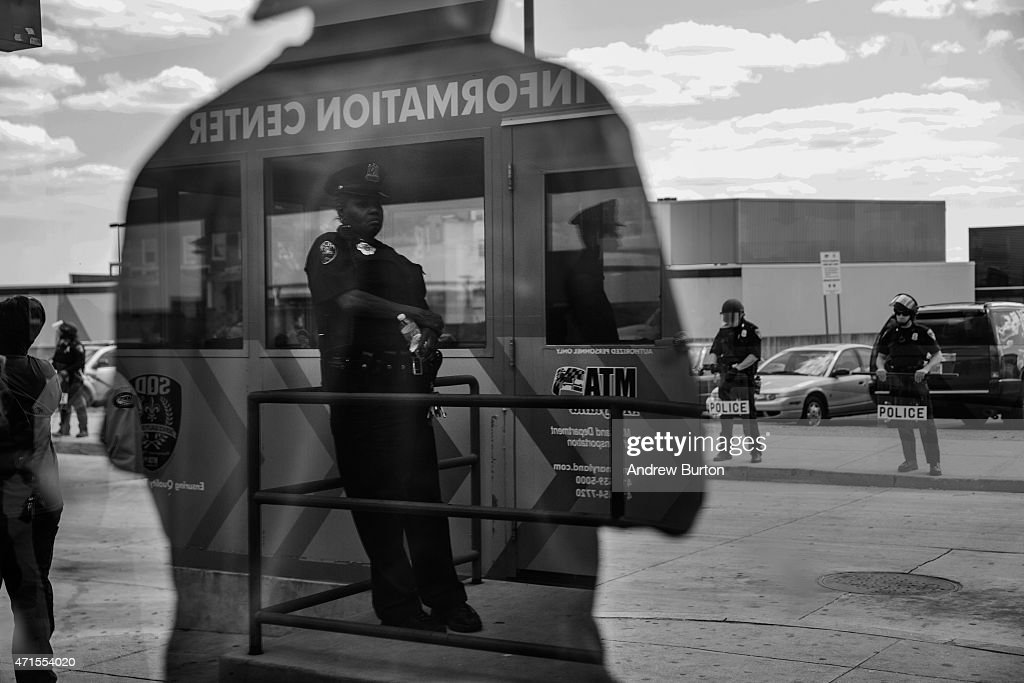 People wait for the bus at the Mondawmin Station while police secure Mondawmin Mall on April 29, 2015 in Baltimore, Maryland. Mondawmin Mall was looted by people Monday afternoon, the same day as the funeral for Freddie Gray. Gray, 25, was arrested for possessing a switch blade knife April 12 outside the Gilmor Houses housing project on Baltimore's west side. According to his attorney, Gray died a week later in the hospital from a severe spinal cord injury he received while in police custody.