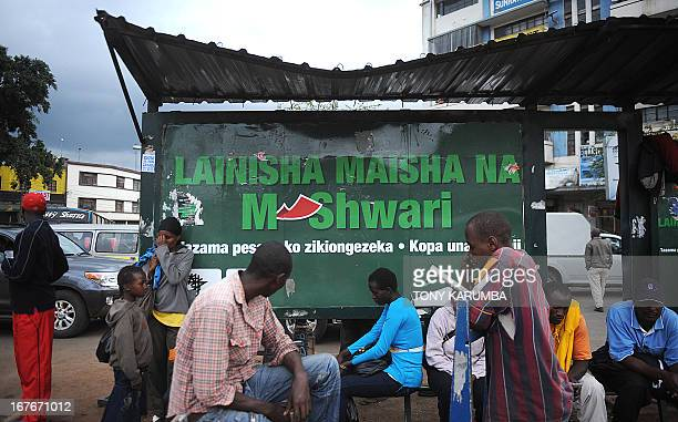 People wait for the bus near an advertisement for a new mobile telephonebased banking initiative called MShwari in the Kenyan capital Nairobi on...
