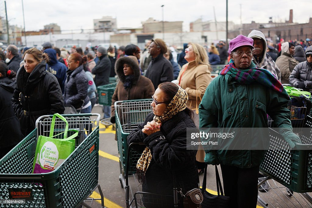 People wait for the doors to open at the newly re-opened Fairway Market on the waterfront in Red Hook on March 1, 2013 in Brooklyn borough of New York City. Fairway, which quickly became a popular shopping destination an an anchor in the struggling community of Red Hook, was closed following severe flooding during Hurricane Sandy on October 29, 2012. Like the rest of Red Hook, Fairway has struggled to quickly re-open in a neighborhood that lost dozens of businesses during the storm. The re-opening, which included a ceremony and ribbon cutting featuring Miss America and Mayor Michael Bloomberg, is being trumpeted as the Red Hook neighborhood's official comeback since the storm.