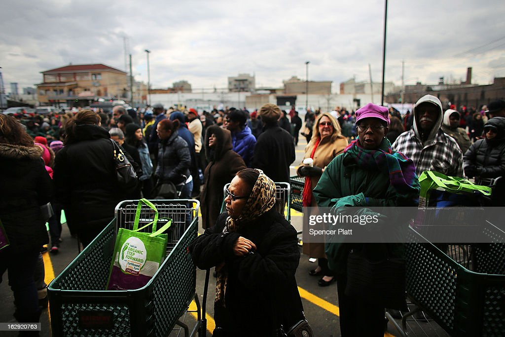 People wait for the doors to open at the newly re-opened Fairway Market on the waterfront in Red Hook on March 1, 2013 in the Brooklyn borough of New York City. Fairway, which quickly became a popular shopping destination and an anchor in the struggling community of Red Hook, was closed following severe flooding during Hurricane Sandy on October 29, 2012. Like the rest of Red Hook, Fairway has struggled to quickly re-open in a neighborhood that lost dozens of businesses during the storm. The re-opening, which included a ceremony and ribbon cutting featuring Miss America and Mayor Michael Bloomberg, is being trumpeted as the Red Hook neighborhood's official comeback since the storm.