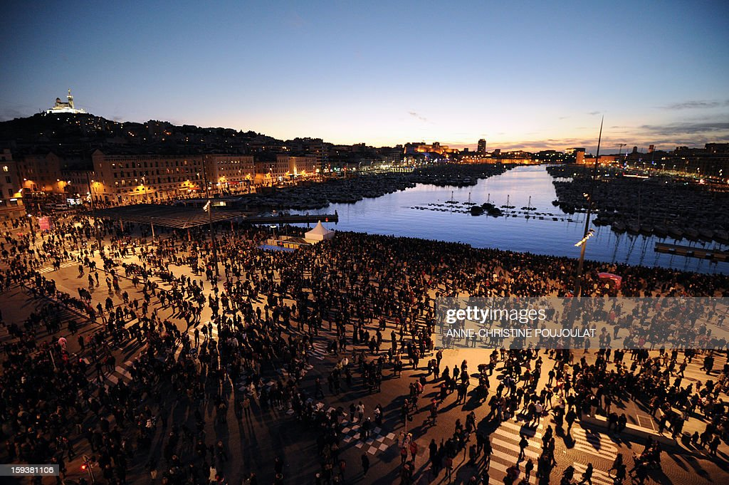 People wait for the light parade in front of the Vieux-Port harbour on January 12, 2013 in the French southern city of Marseille, as part of the launching of Marseille-Provence 2013 European Capital of Culture. The event marks the start of a year, leading to a cultural renaissance in France's second-largest metropolitan area.