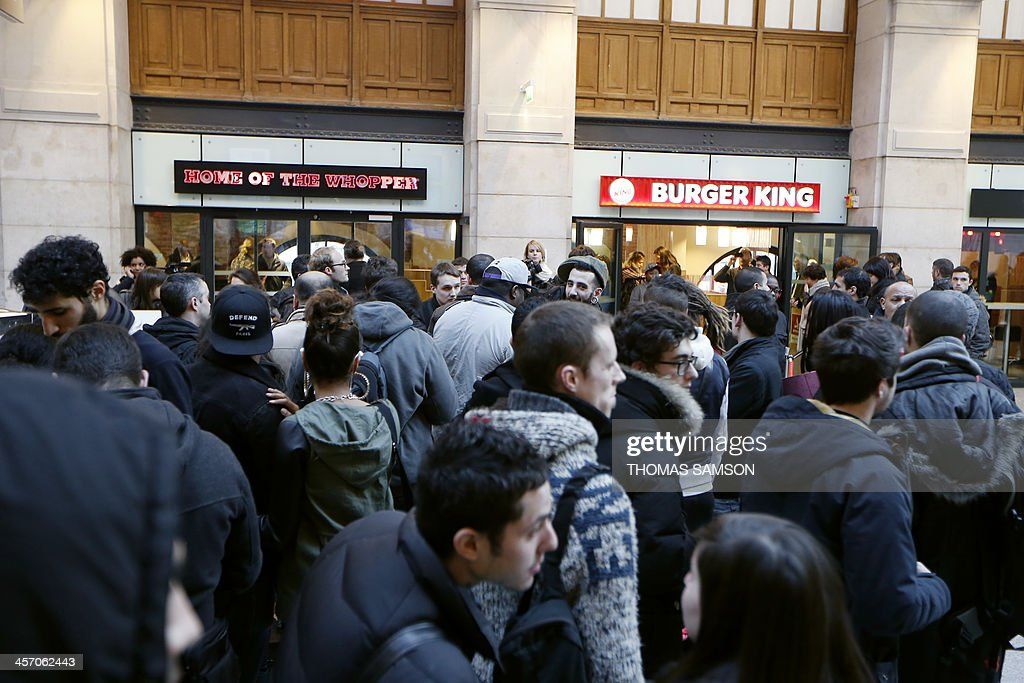 People wait for the opening of a Burger King store at Saint-Lazare railway station in Paris, on December 16, 2013. It is the fourth Burger King store to open its doors in France (the first in Paris), since the group returned in the country, last year. AFP PHOTO / THOMAS SAMSON