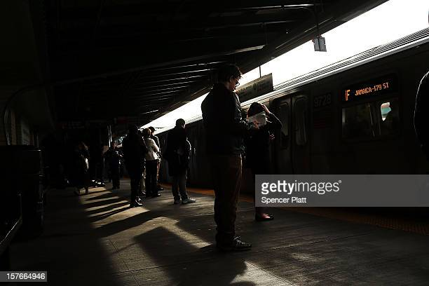 People wait for the subway at a stop in Brooklyn two days after a man was pushed to his death in front of a train on December 5 2012 in New York City...