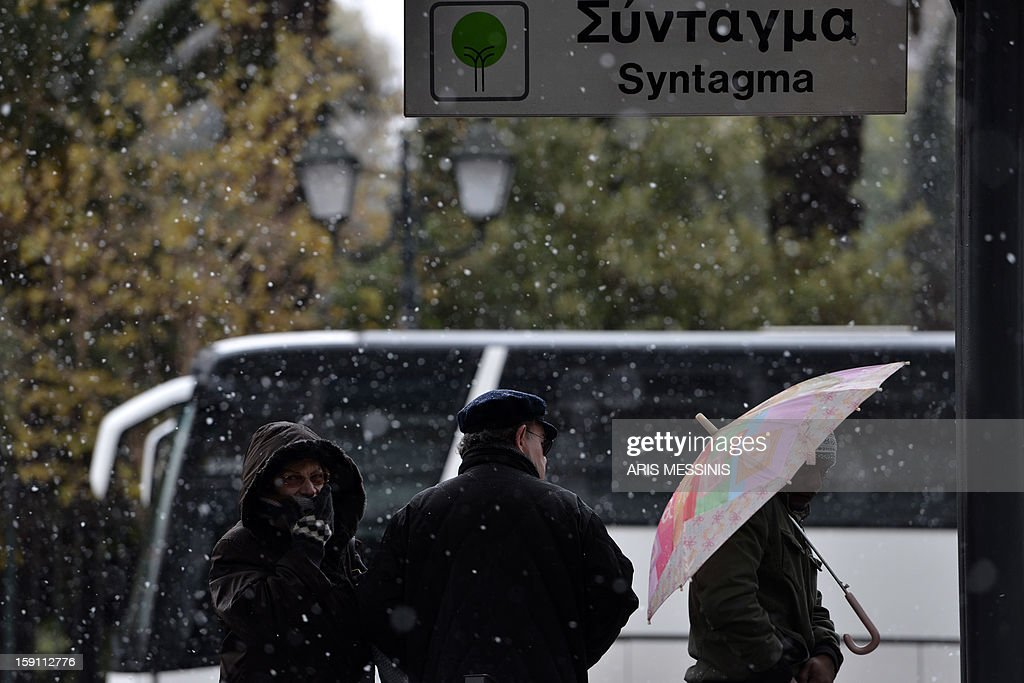 People wait for the tram in central Athens during a snowfall on January 8, 2013.