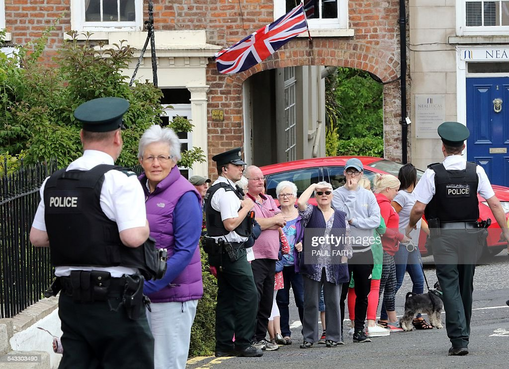 People wait for the visit of Britain's Queen Elizabeth II and Britain's Prince Philip, Duke of Edinburgh to Hillsborough Castle, south of Belfast, where the Royal couple would meet invited guests, including Northern Ireland First and Deputy First Ministers, Arlene Foster and Martin McGuinnes on June 27, 2016 on the start of a two day visit to the province. / AFP / PAUL