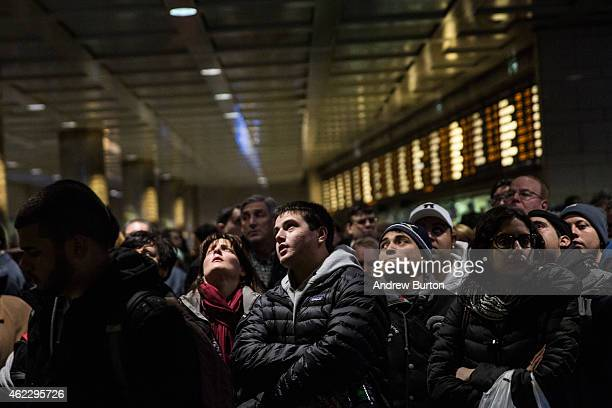 People wait for their train platform to be announced at Penn Station while a major snowstorm begins on January 26 2015 in New York City The storm is...