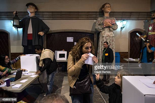 People wait for their turn beneath 'Gegants' giants figures depicting Catalan kings queens and traditional figures to cast their vote at a polling...