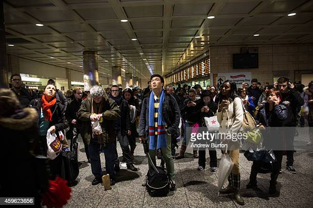 People wait for train information at New York Penn Station during rush hour on the night before Thanksgiving on November 26 2014 in New York City A...