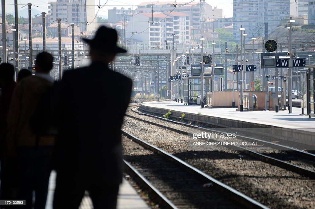 People wait for trains at the Saint Charles train station during a strike by French SNCF railway company employees on June 13, 2013, in Marseille. The strike was called by unions hostile to reforms of the train services sector recently proposed by the French government on May 29.