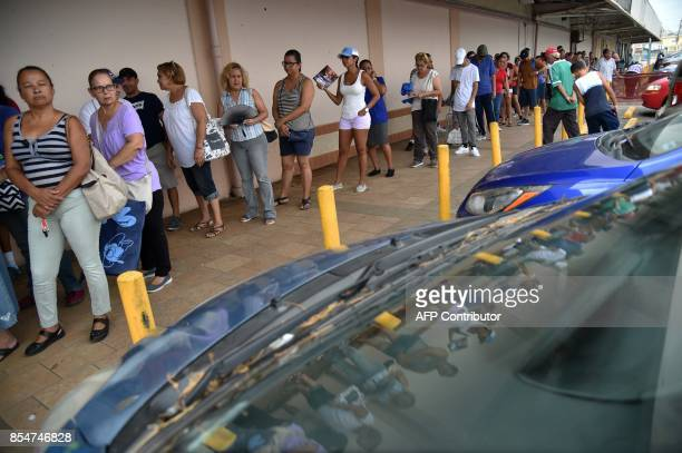 People wait in a line to buy food at a supermarket in Humacao in the east of Puerto Rico on September 27 2017 The US island territory working without...