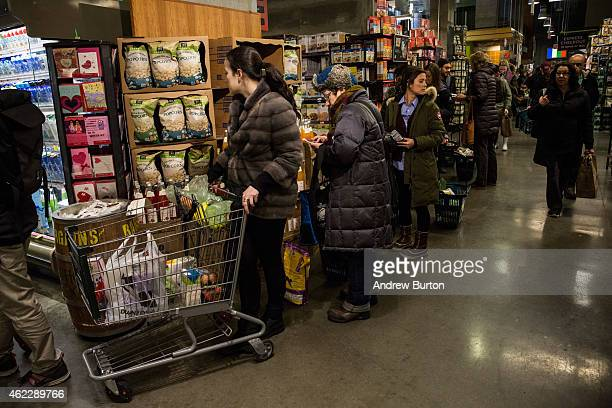 People wait in a long line at Whole Foods while a major snowstorm begins on January 26 2015 in New York City The storm is expected to bring 13 feet...