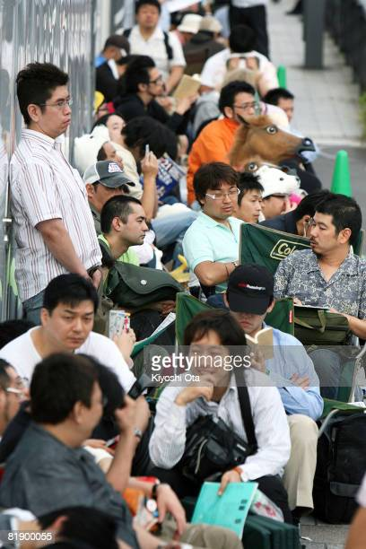 People wait in a queue to buy the newly released Apple iPhone on the first day of its Japanese launch outside SoftBank Mobile's flagship store on...