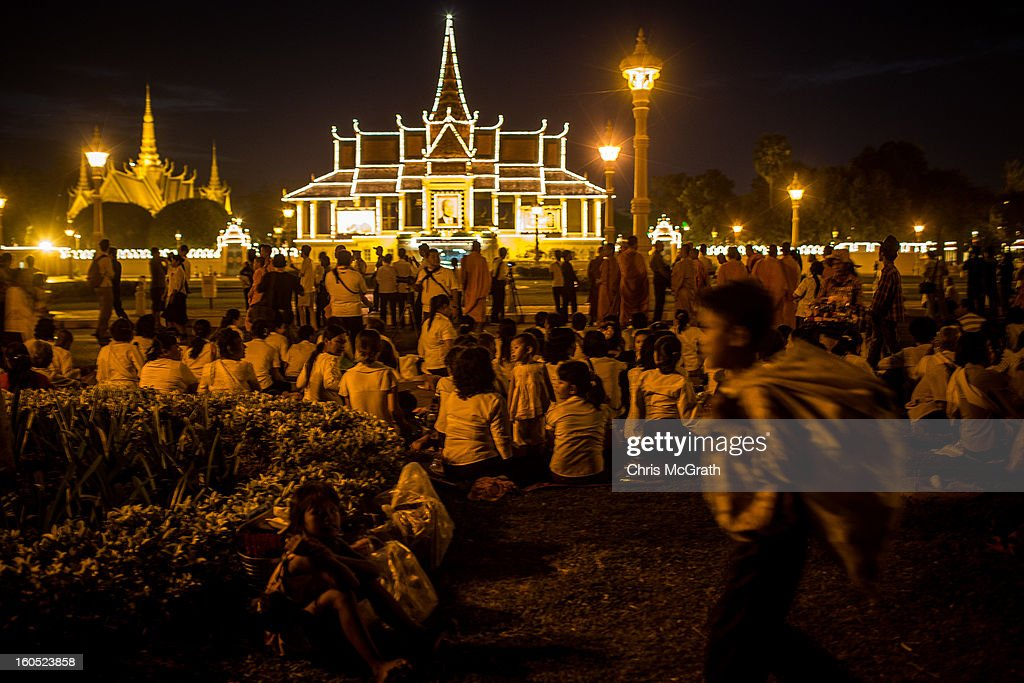 People wait in a roadside park outside the Royal Palace for a ceremony involving King Norodom Sihamoni to finish before police let them onto the grounds to pay their respects to former King Norodom Sihanouk on February 2, 2013 in Phnom Penh, Cambodia. The former kings coffin was transported to the cremation site yesterday after being paraded through the capital in a lavish funeral procession. The cremation will take place on Monday the 4th of February, the funeral pyre will be lit by his wife and son King Norodom Sihamoni.
