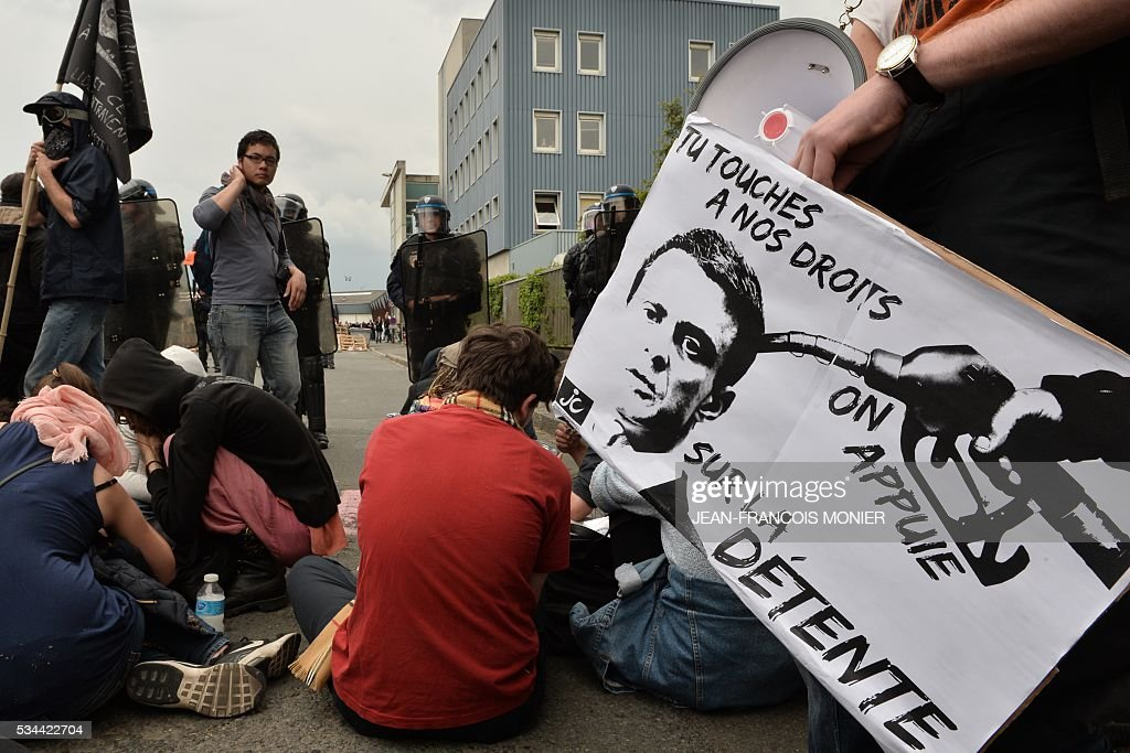People wait in front of French riot police during a protest against the government's labour market reforms in Rennes, on May 26, 2016. The French government's labour market proposals, which are designed to make it easier for companies to hire and fire, have sparked a series of nationwide protests and strikes over the past three months.