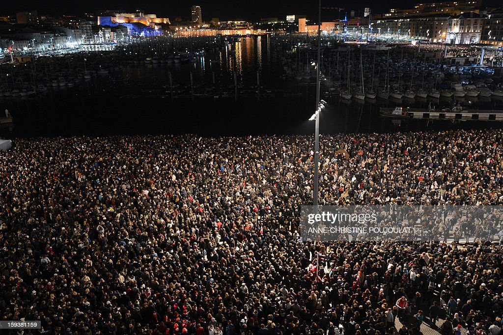 People wait in front of the Vieux-Port harbour on January 12, 2013 in the French southern city of Marseille, for the launching of Marseille-Provence 2013 European Capital of Culture. The event marks the start of a year, leading to a cultural renaissance in France's second-largest metropolitan area. AFP PHOTO / ANNE-CHRISTINE POUJOULAT