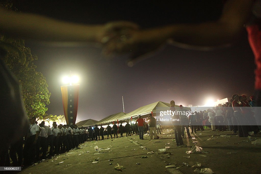 People wait in line after dark (R) to view the remains of late Venezuelan President Hugo Chavez as workers hold hands to maintain the line outside the Military Academy on March 7, 2013 in Caracas, Venezuela. Countless Venezuelans waited on a mile-long line to pay their last respects to Chavez before his funeral tomorrow.