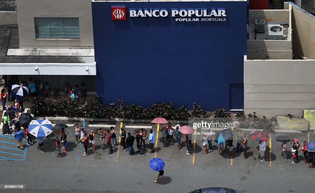People wait in line at a bank as they deal with the aftermath of Hurricane Maria on September 25, 2017 in San Juan Puerto Rico. Maria left widespread damage across Puerto Rico, with virtually the whole island without power or cell service.