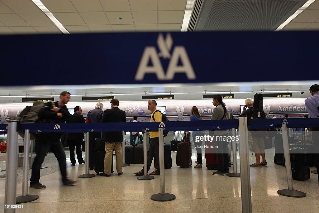 People wait in line at the American Airlines ticket counter in the Miami International Airport on February 12, 2013 in Miami, Florida. Reports indicate that a deal between American Airlines and US Airways to merge is set to be announced as early as tomorrow. If the deal goes through it would create the world's biggest airline.