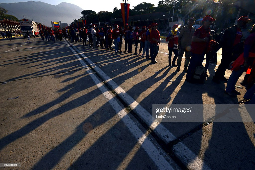 People wait in line before the start of the funeral for Venezuelan President Hugo Chavez outside the Military Academy on March 8, 2013 in Caracas, Venezuela. President Chavez will be embalmed an transferred to a specially built mausoleum in the Military History Museum in Caracas.