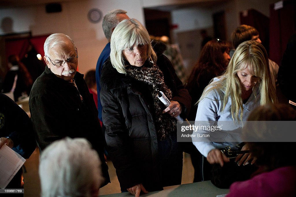People wait in line, by the light of generators, to vote at Silver Bay Elementary School on November 6, 2012 in Toms River, United States. The Elementary school, which usually hosts voting for two districts, accommodated voting for seven districts today due damage caused by Hurricane Sandy; the entire voting system at the school was also run off of generators, due to a loss of power.