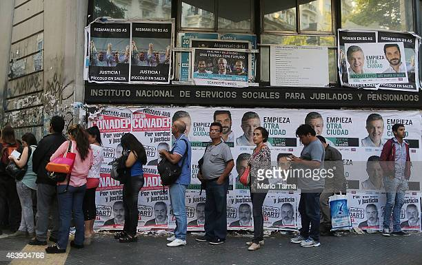 People wait in line for a bus along Avenida de Mayo in front of political posters on February 19 2015 in Buenos Aires Argentina The street was the...