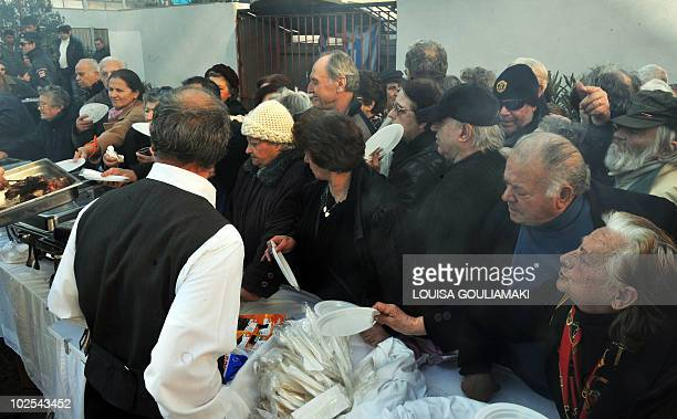 People wait in line for a free grilled meat distribution near a central market in Athens on February 4 2010 The event was organised by the...