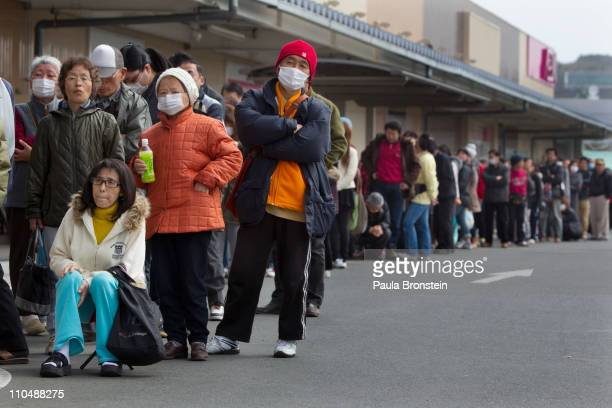 People wait in line for a supermarket to open as limited food continues to cause problems for people in the earthquake effected areas on March 20...