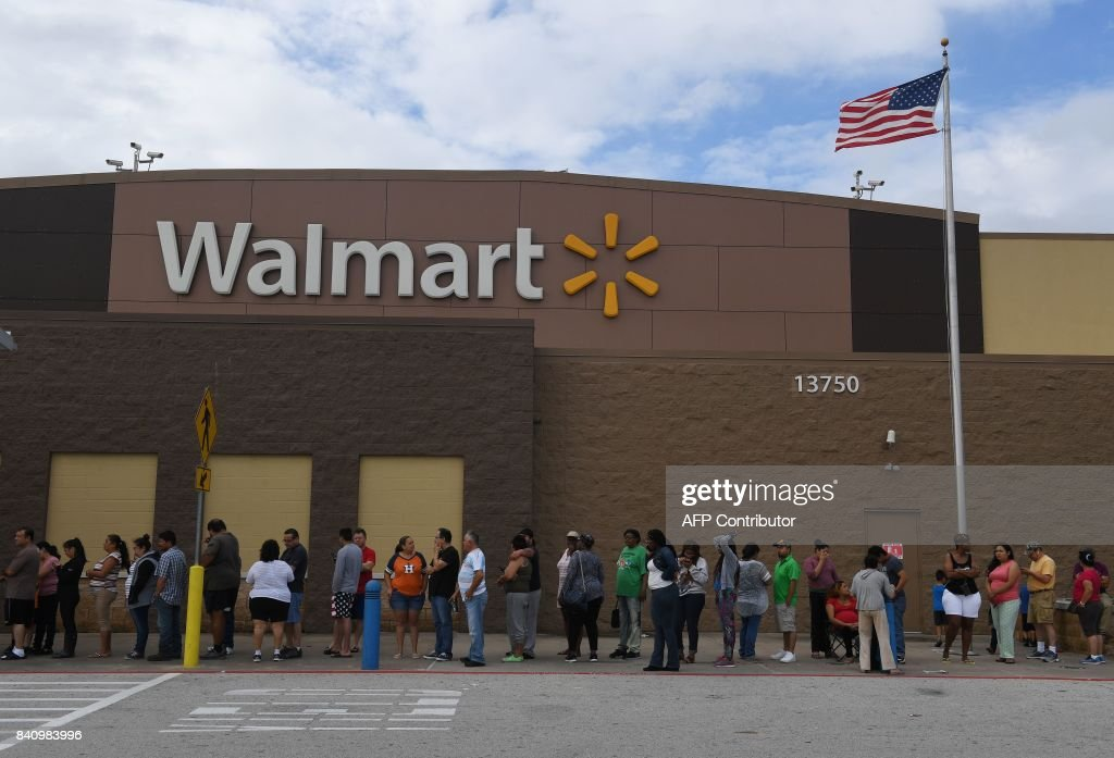 People wait in line for a Walmart store to open after Hurricane Harvey caused heavy flooding in Houston, Texas on August 30, 2017. Monster storm Harvey made landfall again Wednesday in Louisiana, evoking painful memories of Hurricane Katrina's deadly strike 12 years ago, as time was running out in Texas to find survivors in the raging floodwaters. /