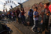 People wait in line in front of an amusement park located more than a kilometer away to view the body of deceased Venezuelan President Hugo Chavez on...