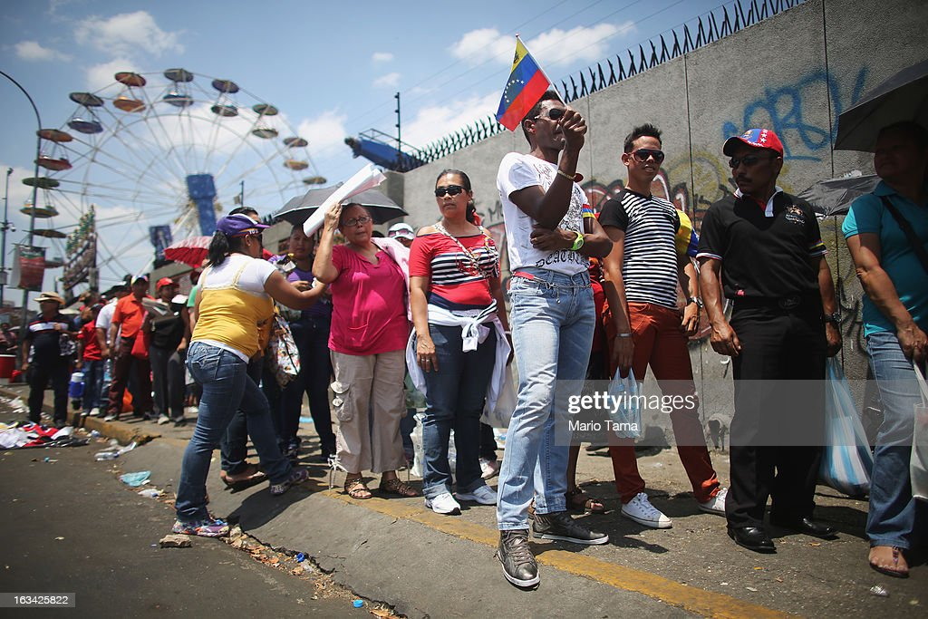 People wait in line in front of an amusement park located more than a kilometer away to view the body of deceased Venezuelan President Hugo Chavez on March 9, 2013 in Caracas, Venezuela. Venezuelans continue to wait in line for hours to pay their last respects to Chavez on the day after his funeral. Venezuela's elections commission has set April 14 as the date for voting to replace the late Chavez.